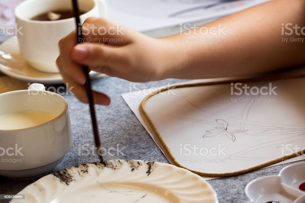someone drawing on paper fan stock photo