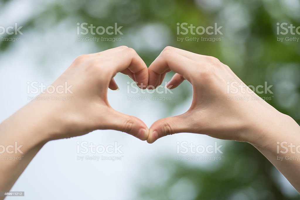 Someone forms a heart shape with his hands to show love stock photo