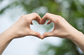 Someone forms a heart shape with his hands to show love