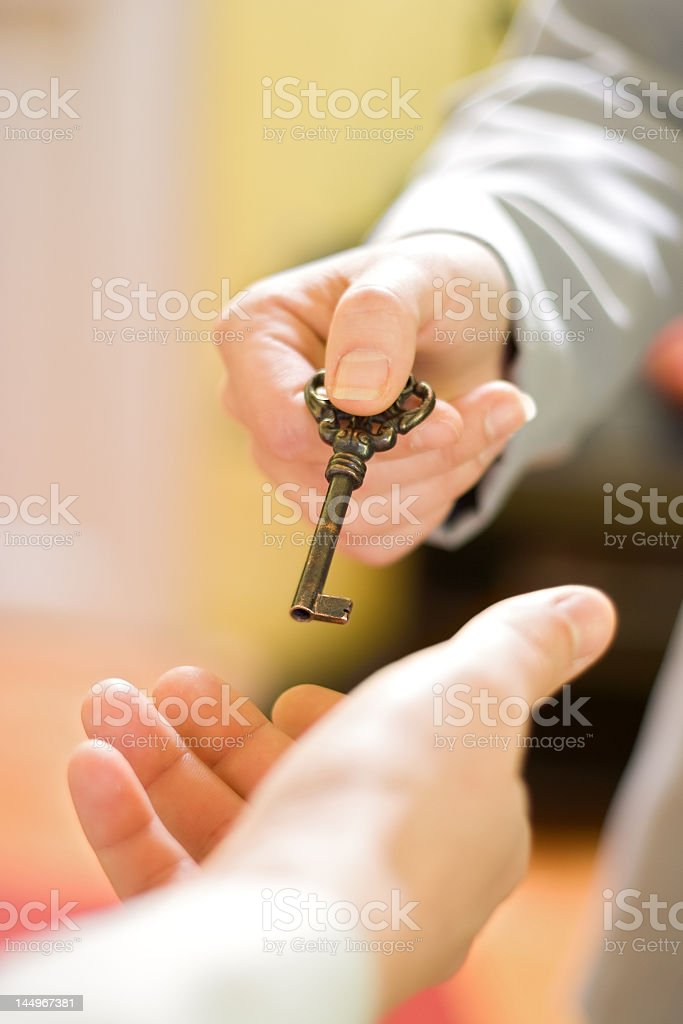 Someone handing a vintage brass key to another person royalty-free stock photo
