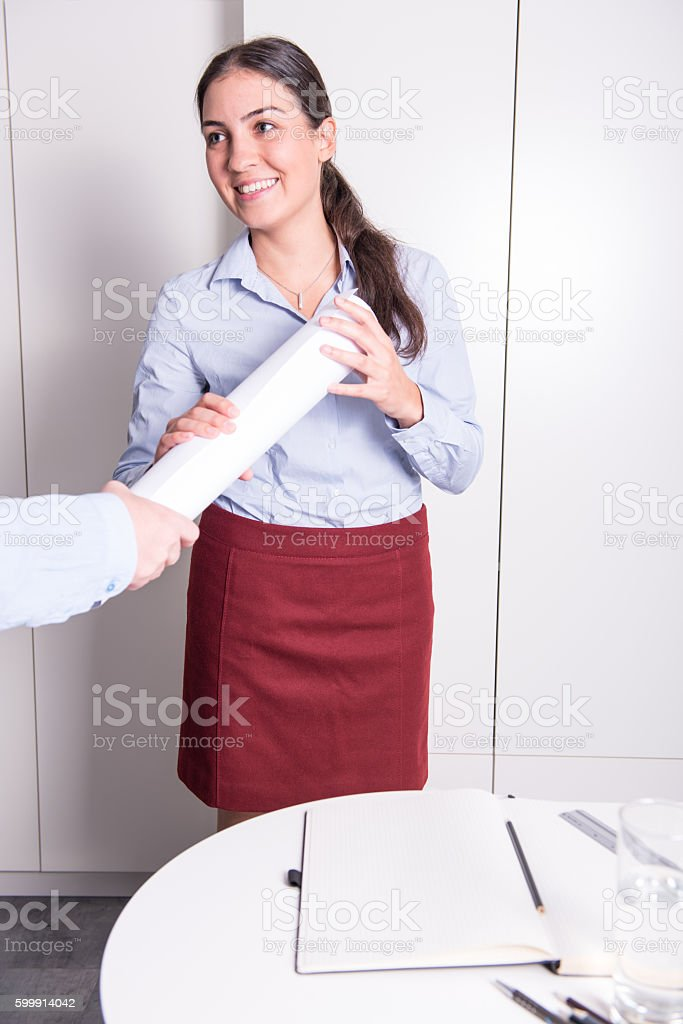 someone is giving rolled drawing to a young female engineer stock photo