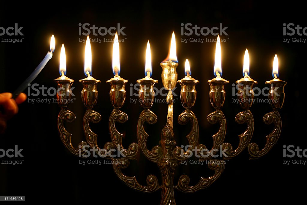 Someone lighting the last candle of a Menorah stock photo