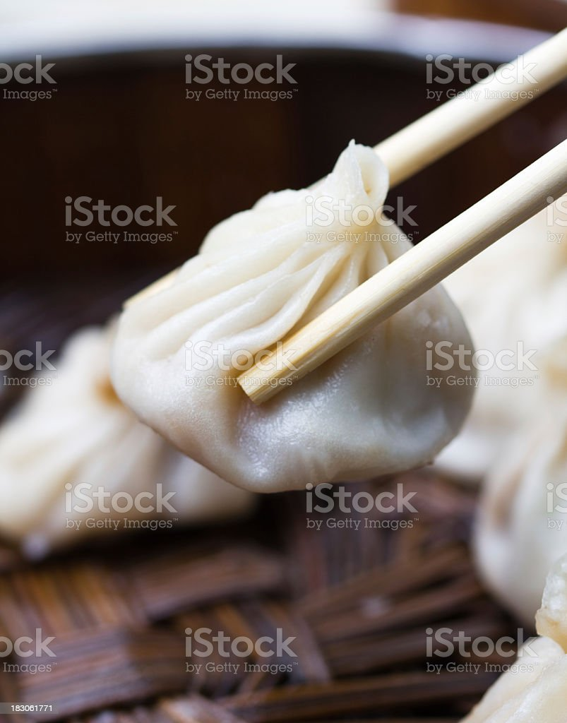 Someone picking up a dumpling with chopsticks stock photo
