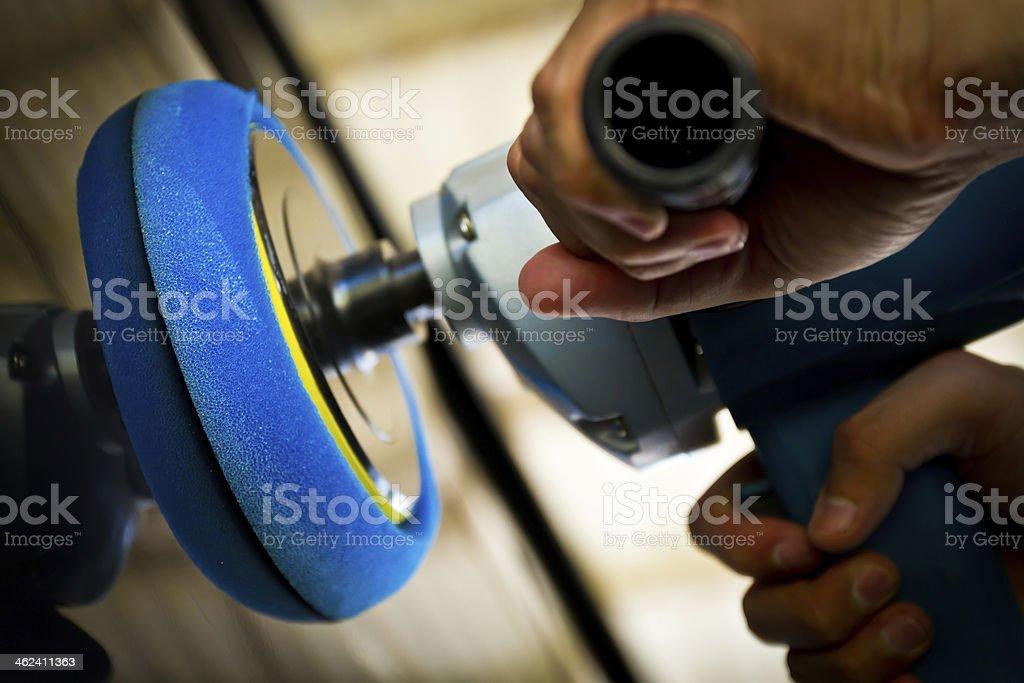 Someone using a handheld car polishing machine  stock photo