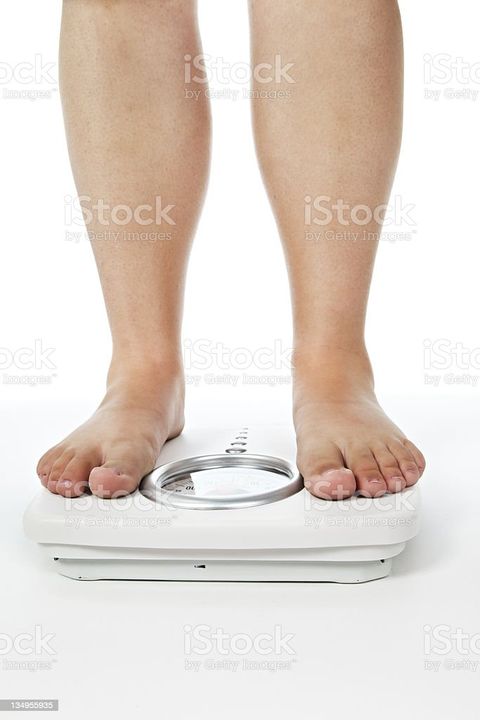 Somewhat overweight legs standing on bathroom scale stock photo