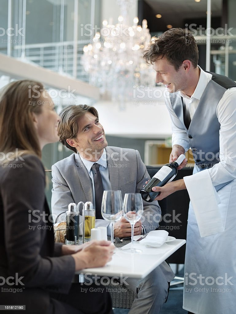 Sommelier presenting wine bottle to couple in restaurant royalty-free stock photo