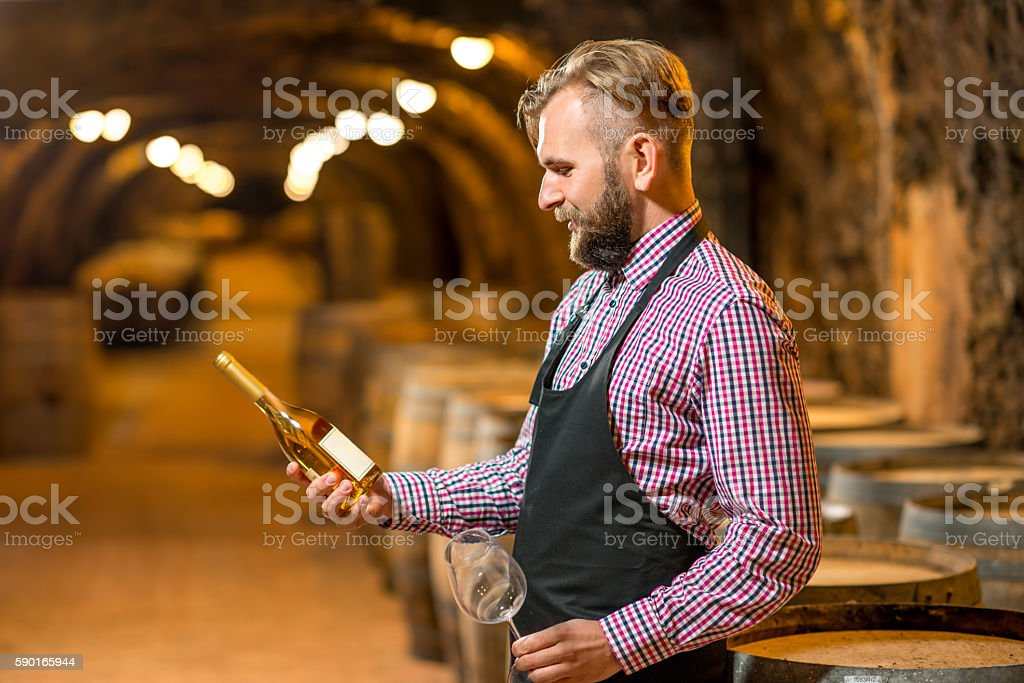 Sommelier with wine bottle in cellar stock photo