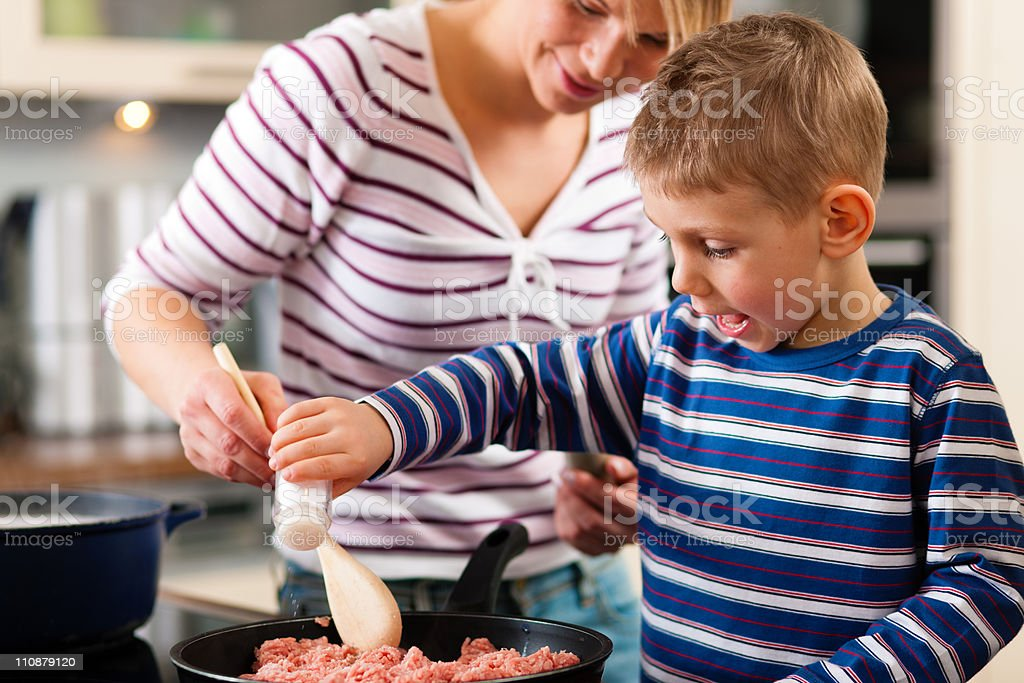 Son adds salt to some ground beef while his mother stirs it stock photo