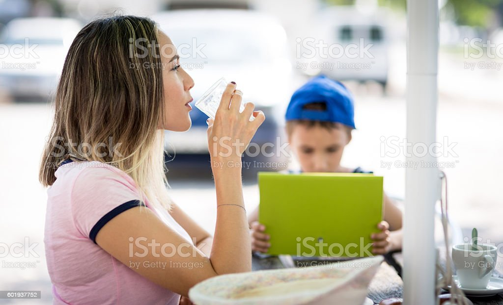 Son and Mom sitting on the street cafe stock photo