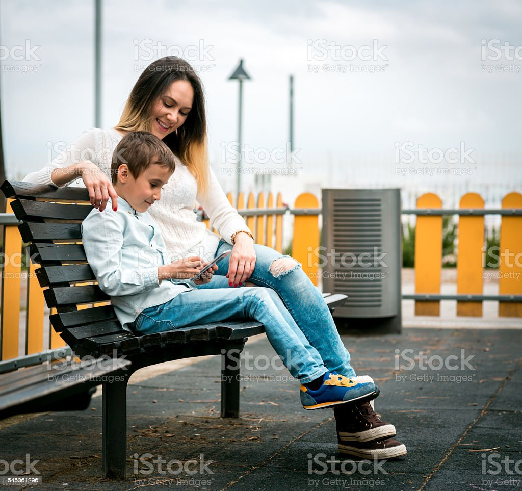 Son and Mom using smartphone stock photo