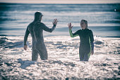 Son and Mother high five in the ocean