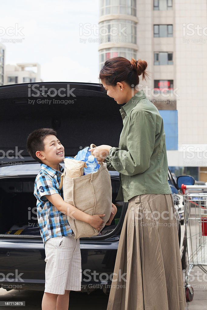 Son and mother putting groceries in car royalty-free stock photo