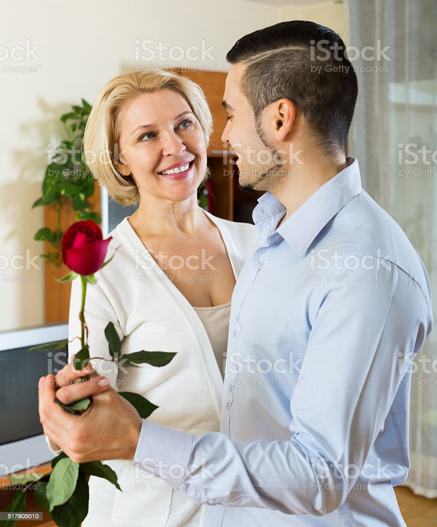 son asking  mother to dance at home stock photo