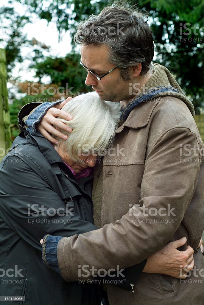 Son comforting his mother stock photo