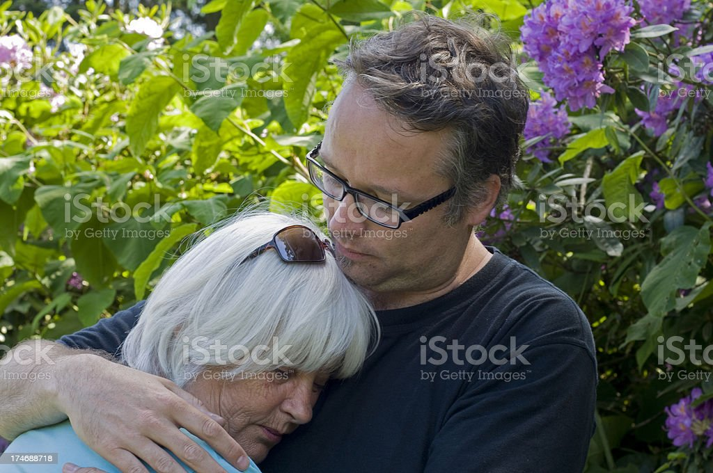 Son consoling and comforting his mother  outdoors royalty-free stock photo