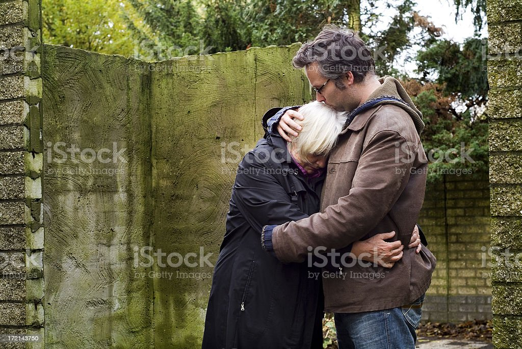 Son consoling his mother stock photo
