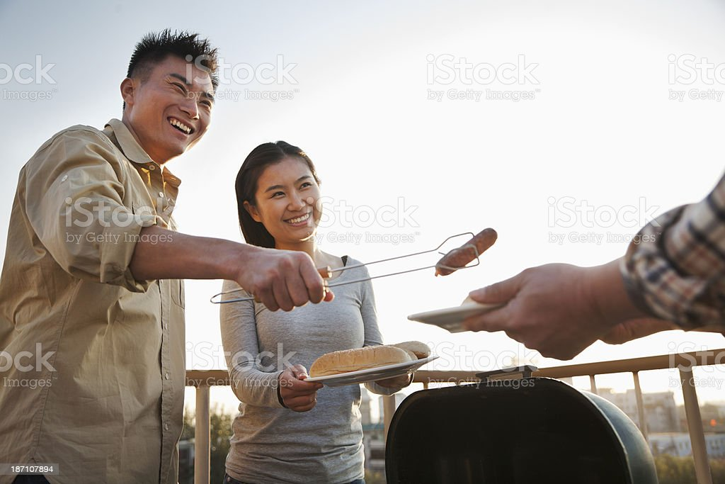 Son giving sausage to his father over the barbeque royalty-free stock photo