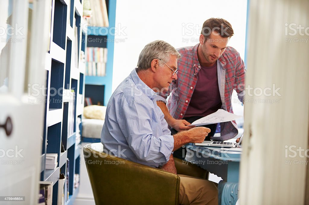 Son Giving Senior Parent Financial Advice In Home Office stock photo