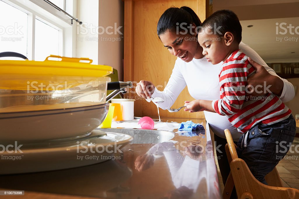Son Helping Mother To Wash Dishes In Kitchen Sink stock photo
