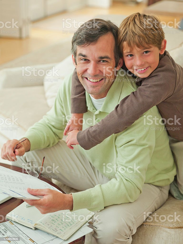 Son hugging father reading paperwork royalty-free stock photo