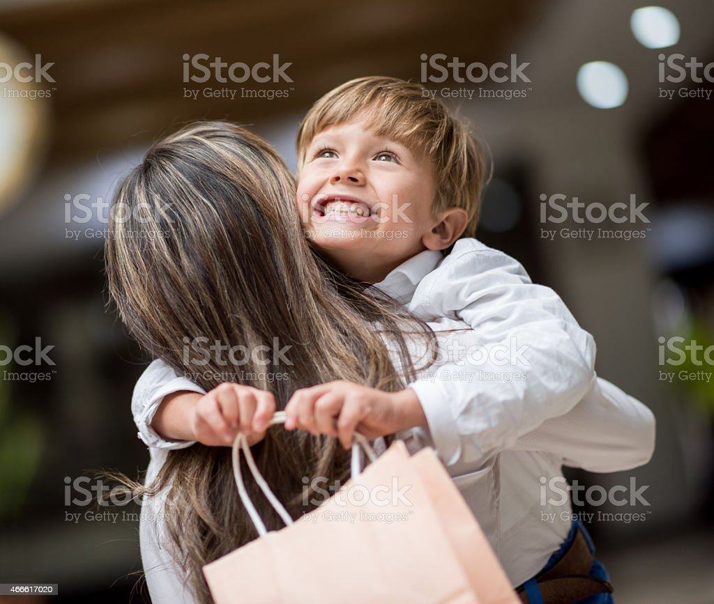 Son hugging mother at the shopping center stock photo