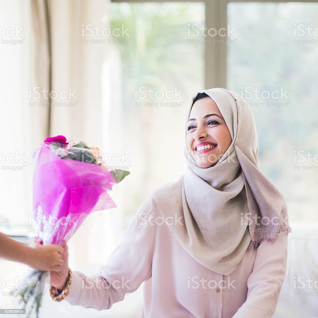 Son is giving flowers to her mother as a present. stock photo