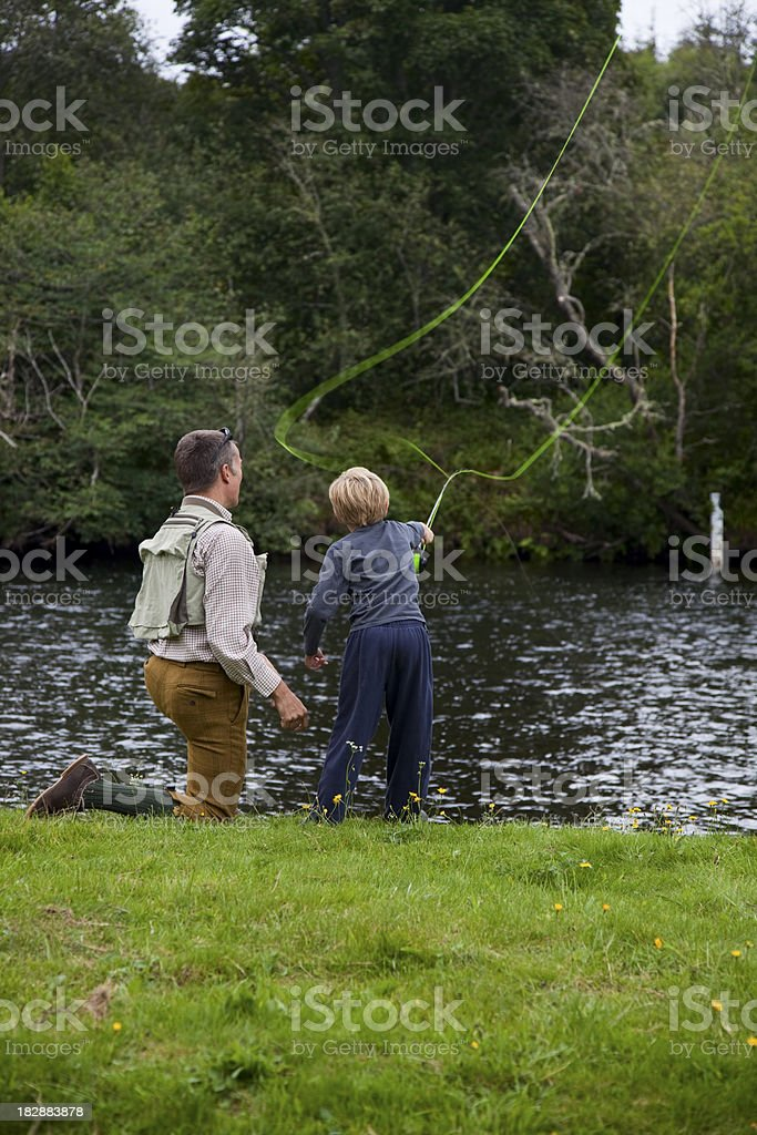 Son learning to fish with dad on the river royalty-free stock photo