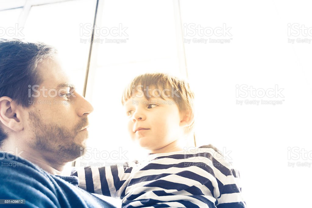 Son looking at his father stock photo