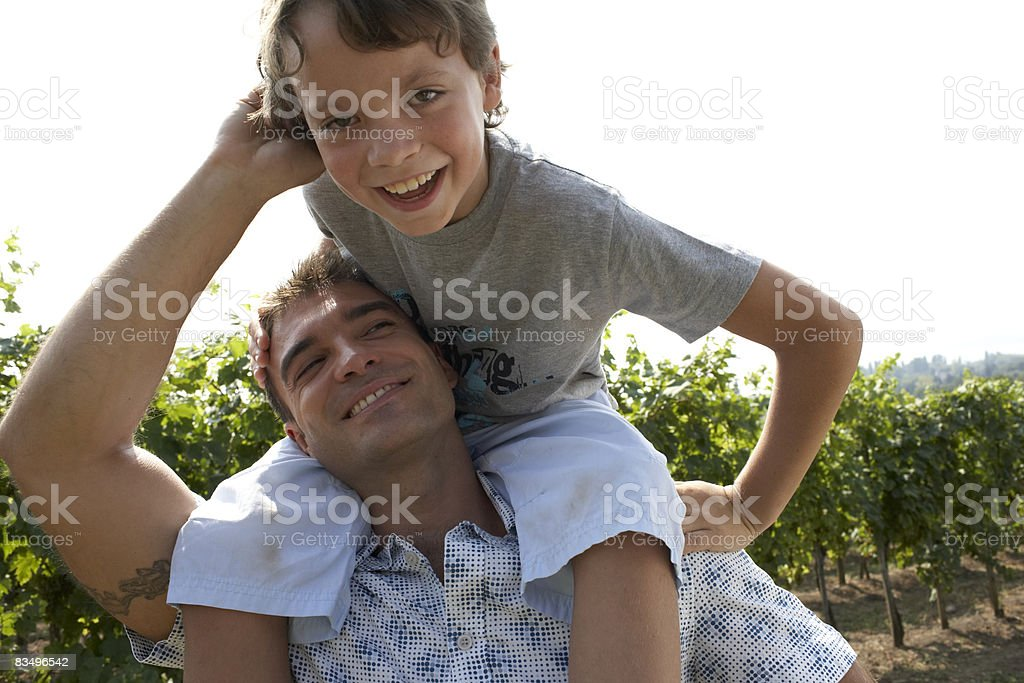 son on father's shoulders stock photo