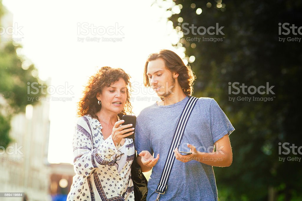Son patiently explains smart phone to his mother stock photo