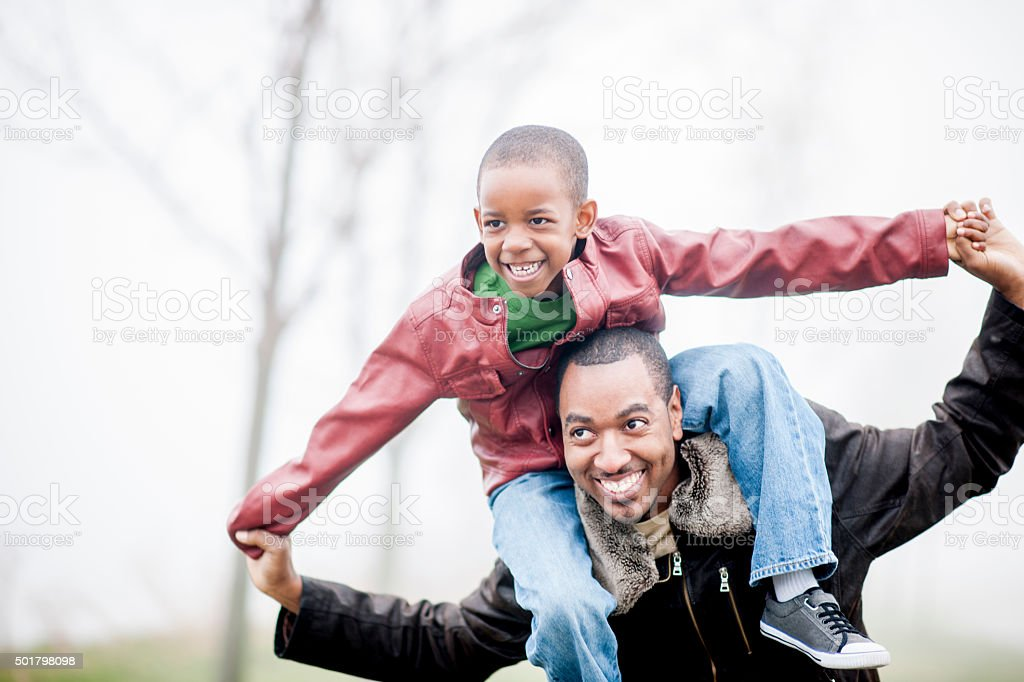 Son Riding on His Father's Shoulders stock photo