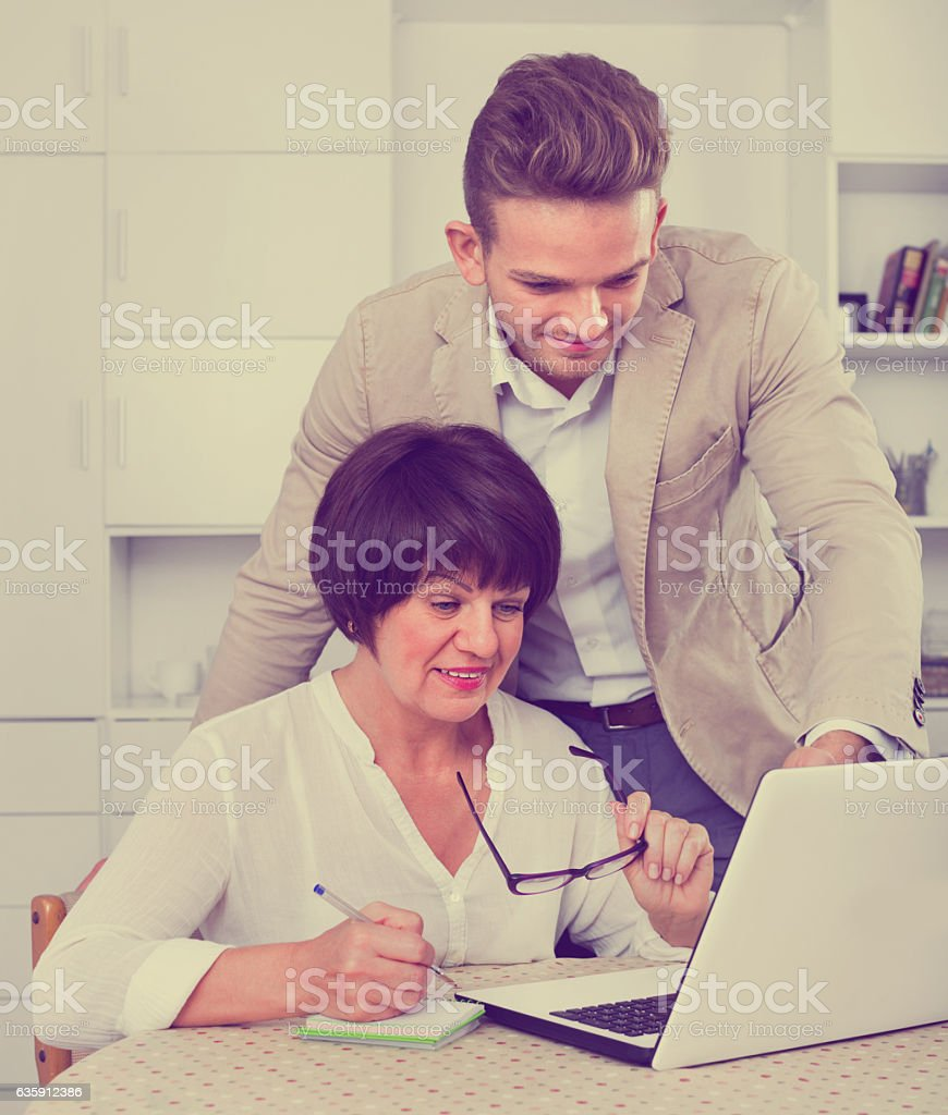 Son shows to his elderly mother new software on laptop stock photo