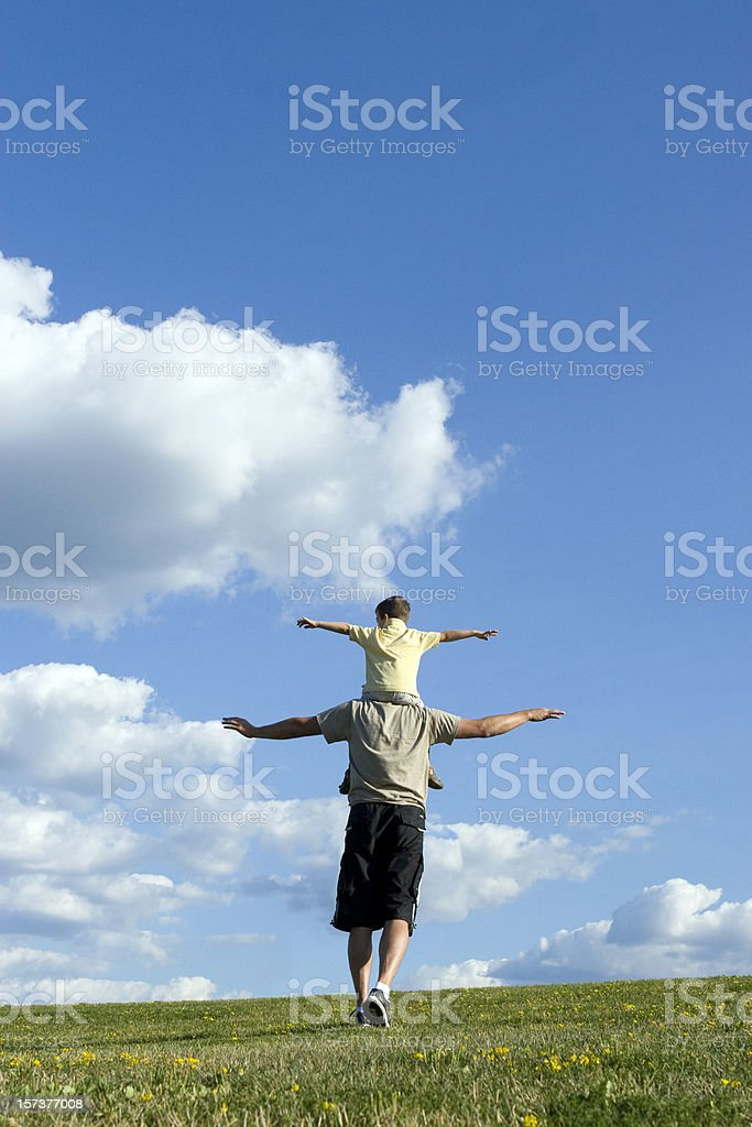Son sitting on fathers shoulders in a field under blue sky  royalty-free stock photo