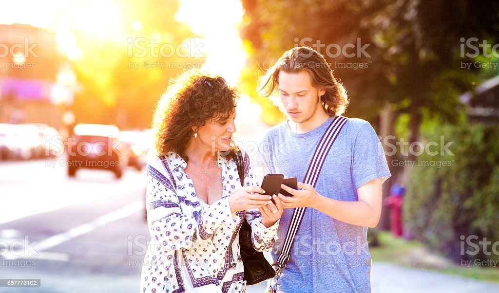 Son teaches his mother how to play mobile game stock photo