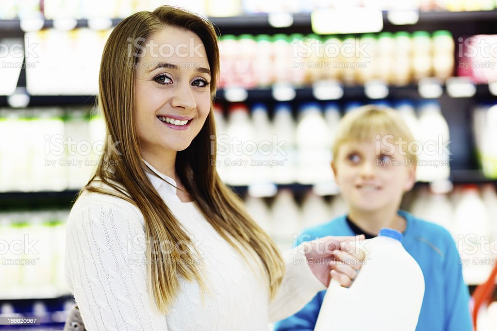 Son watches smiling mother select milk in supermarket royalty-free stock photo