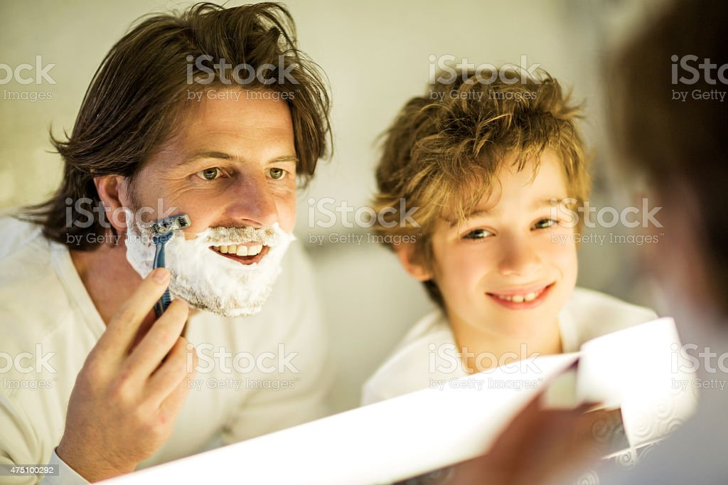 Son watching his father shaving with razor in bathroom. stock photo