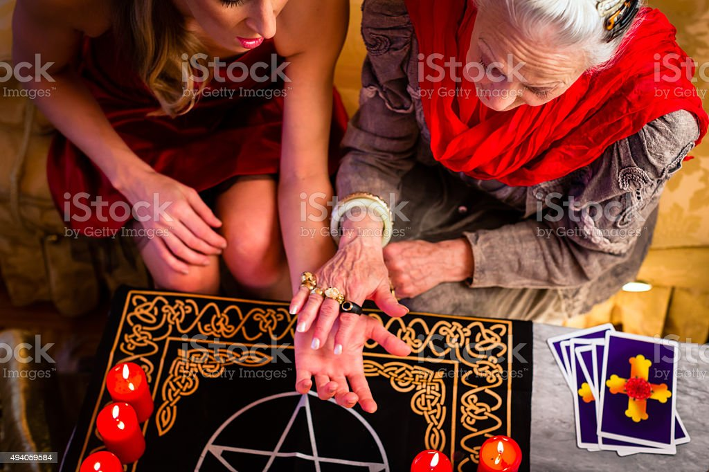 Soothsayer during a session doing palmistry stock photo