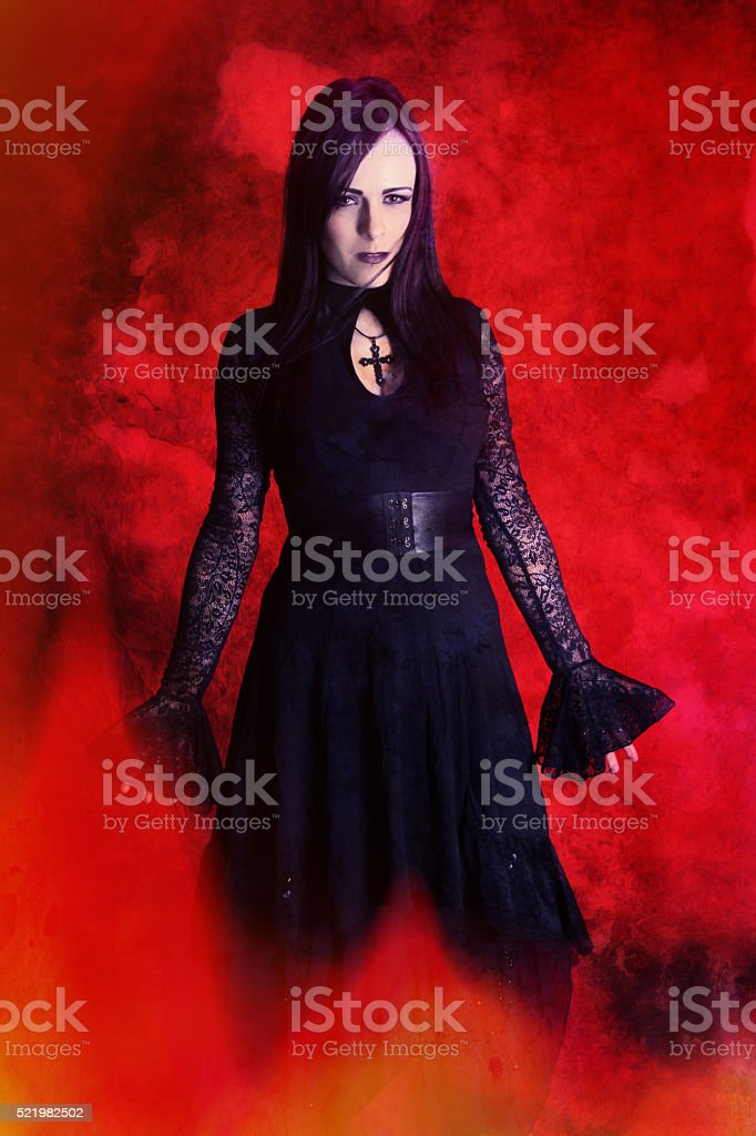Sorceress standing in fire looking at camera, hands down. stock photo
