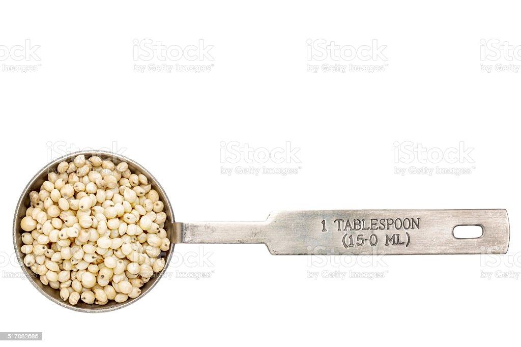 sorghum grain in a tablespoon stock photo