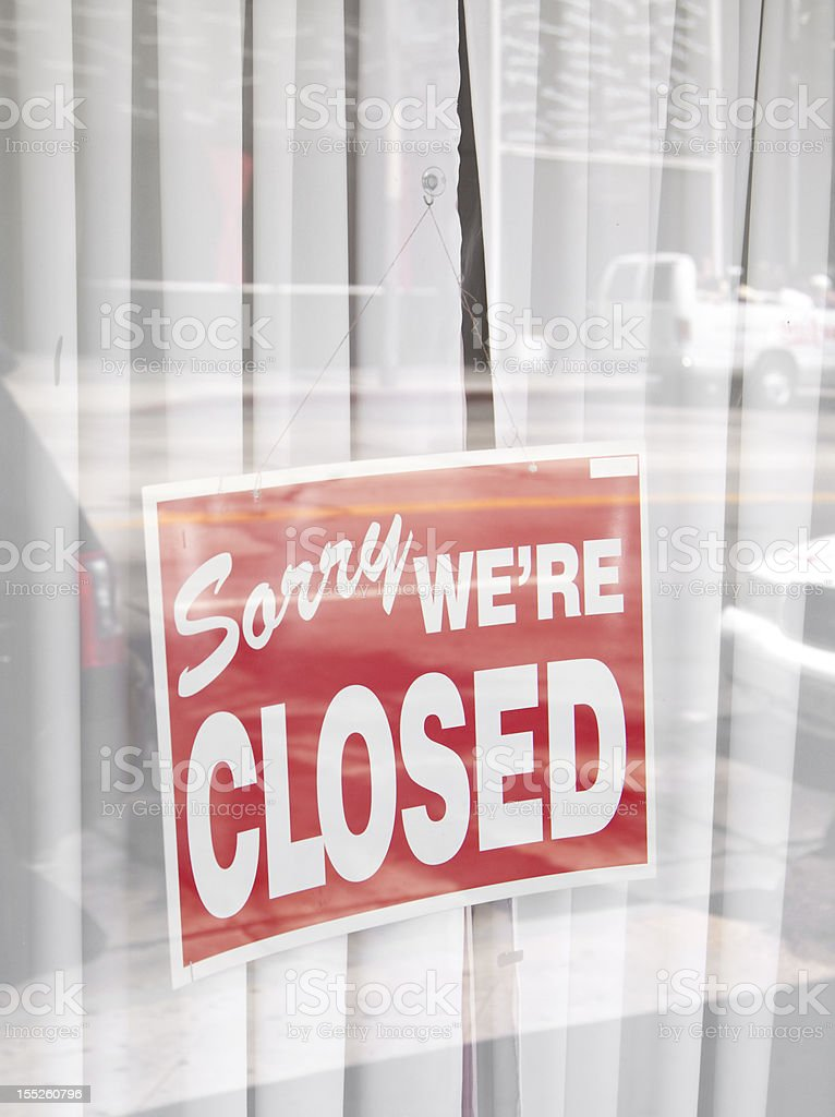 Sorry were closed sign surrounded by reflections of the street royalty-free stock photo