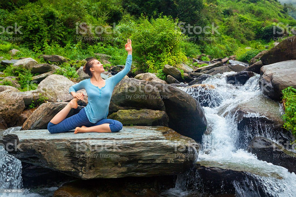 Sorty fit woman doing yoga asana outdoors at tropical waterfall stock photo