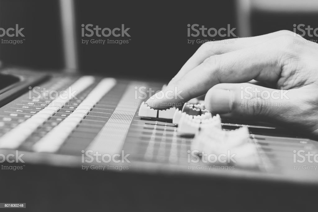 sound engineer hands working on sound mixer, black and white. shallow dept of field stock photo
