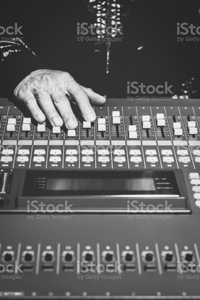 sound engineer hands working on sound mixer in digital music editing studio or live concert, black and white stock photo