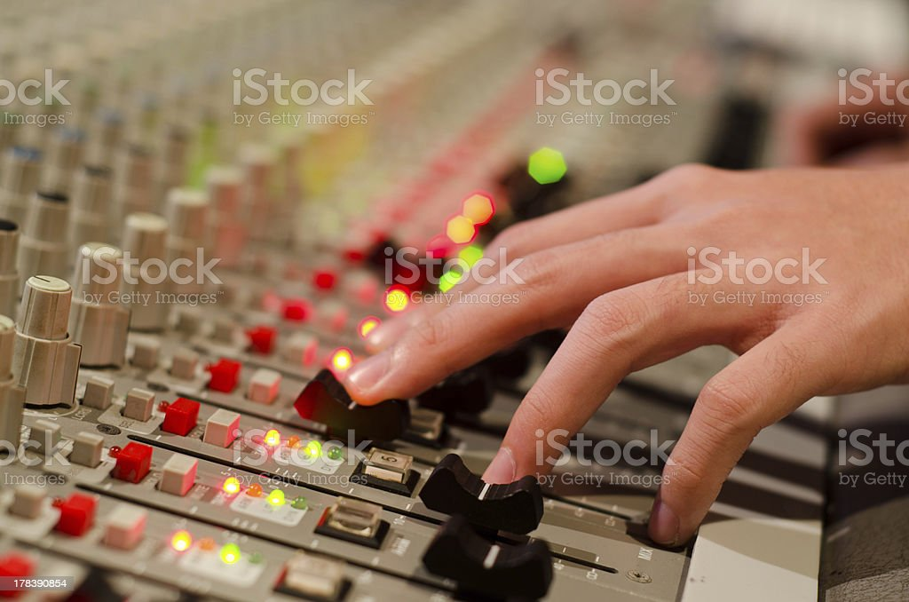 sound engineer's hand moving on mixing board royalty-free stock photo