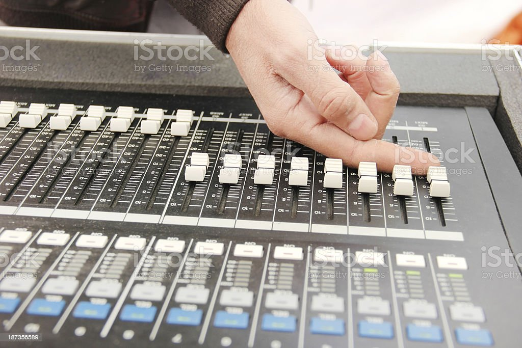 sound engineer's hand moving on mixing board stock photo