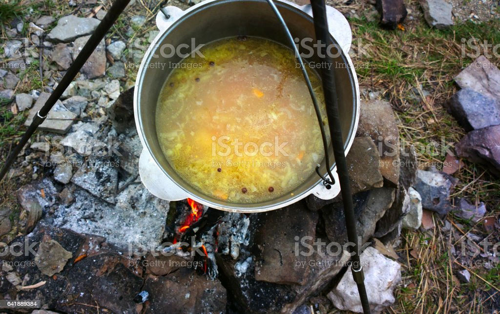 Soup in a cauldron on the fire. stock photo
