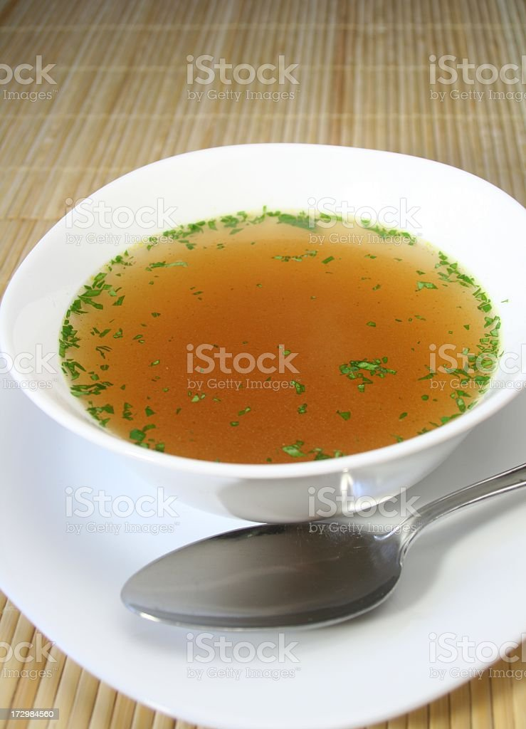 Soup in a white bowl with a silver spoon on the side stock photo