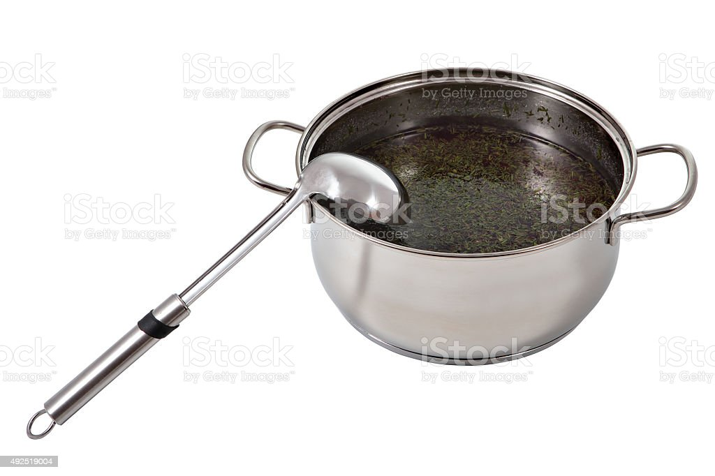 Soup ladle stainless steel lies in a pot of broth. stock photo