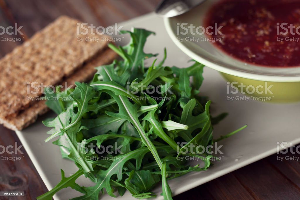 Soup, leaves of arugula and breads are served on a wooden table. stock photo