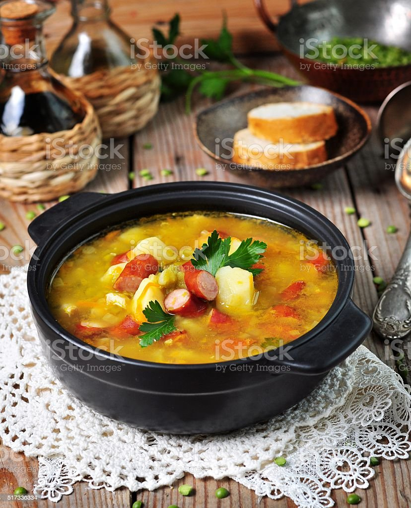 Soup of dry peas, vegetables with smoked sausage stock photo